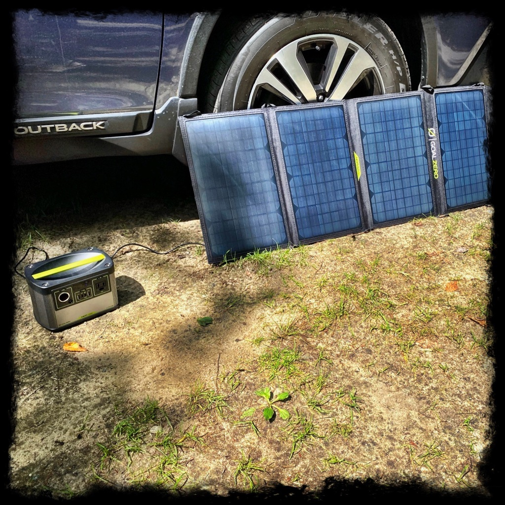 Solar panels leaned against our car in the sun to charge the Yeti