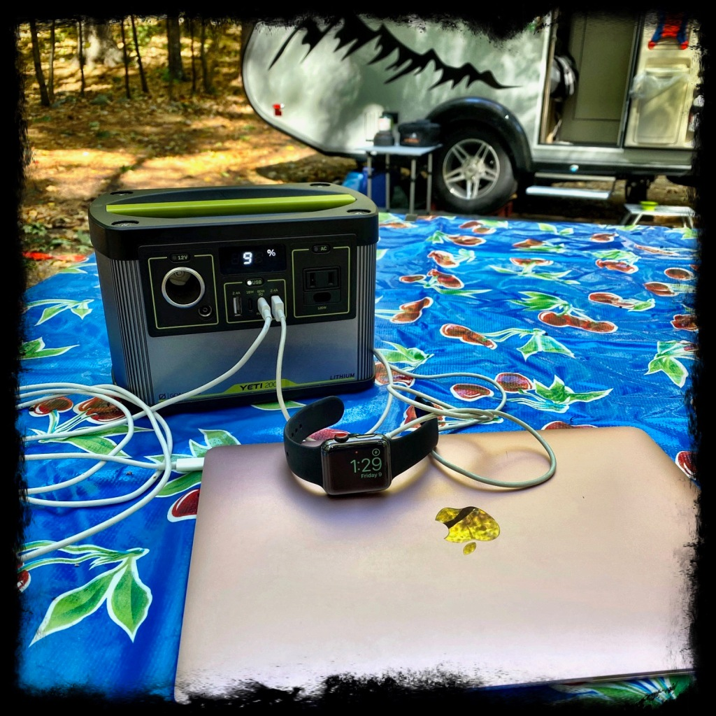 GoalZero Yet with Mac laptop and Apple Watch plugged in to charge on a picnic table near the camper
