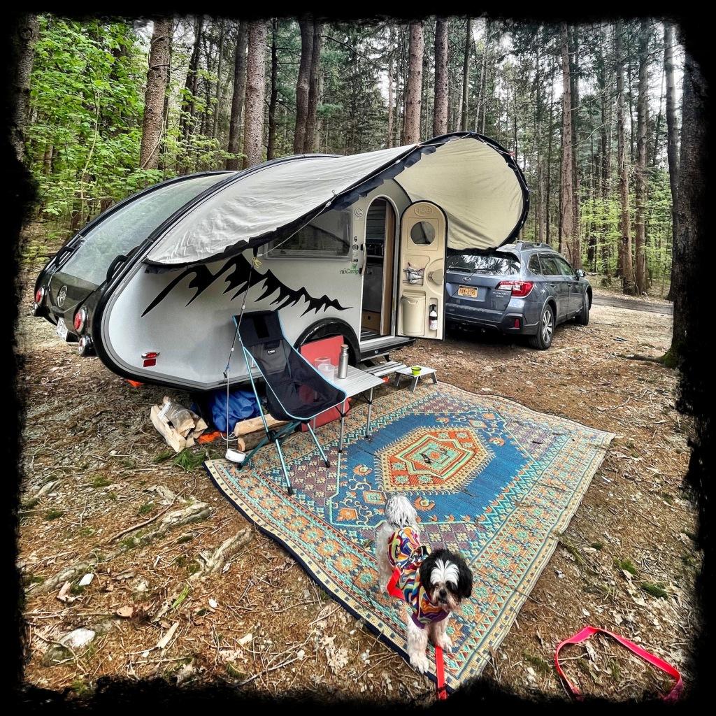 Shih tzu in a coat on a camp rug in front of a camper