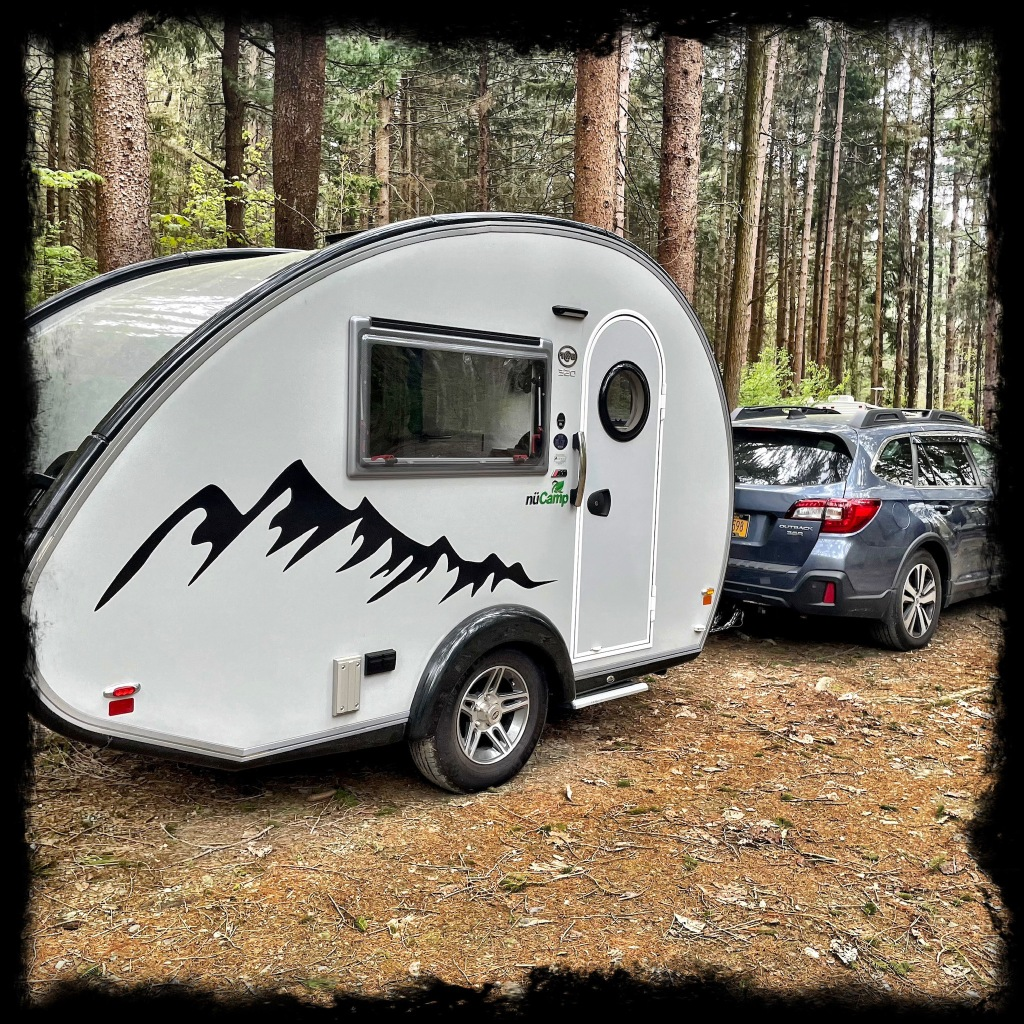 The camper packed up and hitched to a Subaru ready to drive