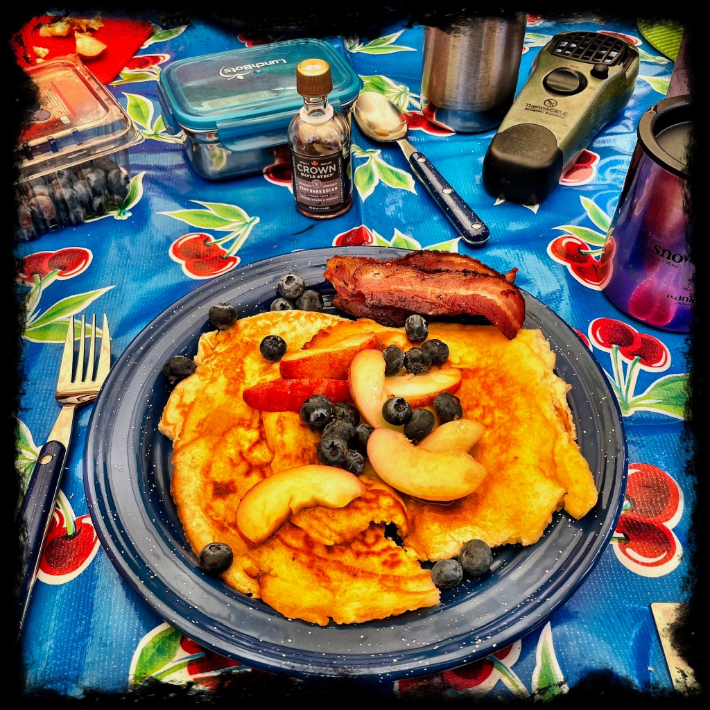 Pancakes with peaches and blueberries on an enamel camping plate
