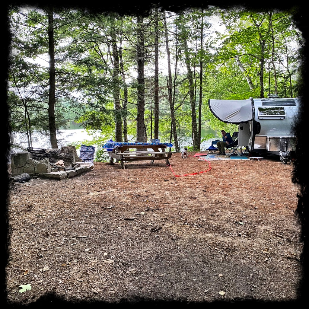 View of Camper at campsite along the edge of the pond