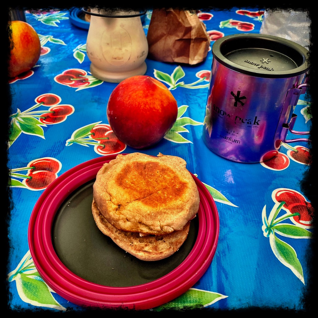 Plate with english muffin breakfast sandwich, peach and coffee