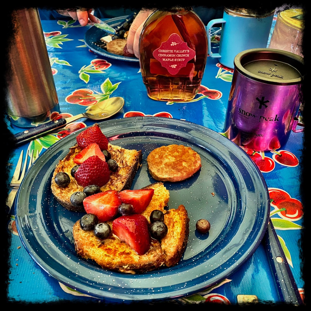 Plate with french toast, strawberries and blueberries with sausage and syrup